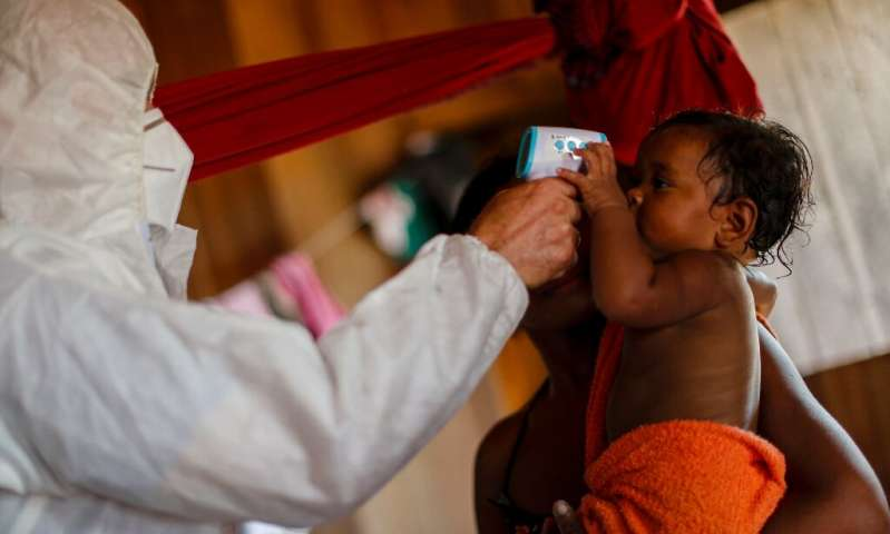 A health worker measures the temperature of riverside residents at the Pindobal community in the Igarape-Miri municipality, Para