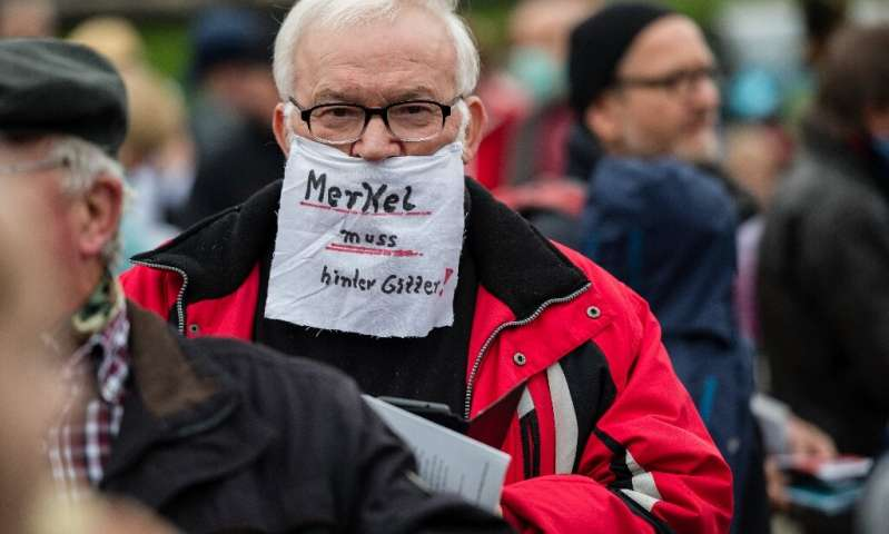 German Chancellor Angela Merkel urged public support for new shutdowns but this protester in Dresden was unimpressed—he says she